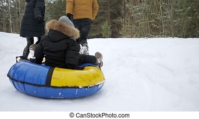 Happy parents are running and sliding their son in tubing in...