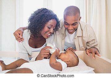 Happy parents feeding their baby boy in his crib