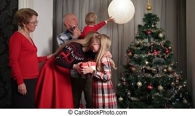 Happy parents giving Christmas present to daugther