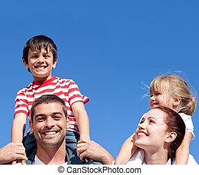 Happy parents giving their children piggyback rid