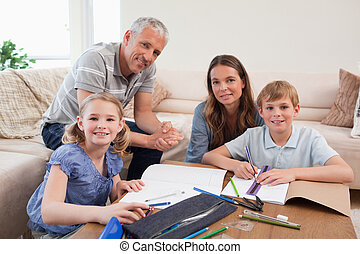 Happy parents helping her children to do their homework in...
