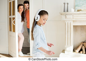 Happy parents looking at cute little girl in white headphones