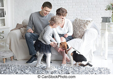 happy parents looking at their daughter, who feeds the dog