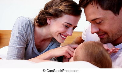 Happy parents lying with their cute baby