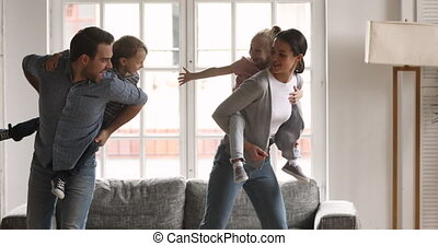 Happy parents piggybacking little kids playing together in living room