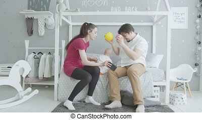 Happy parents playing with infant girl in bedroom
