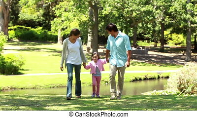 Happy parents playing with their daughter in a parkland