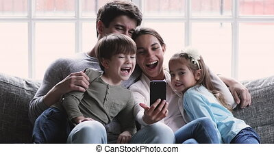 Happy parents recording funny video on cellphone with little children.