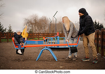 Happy parents riding on the swing with little son