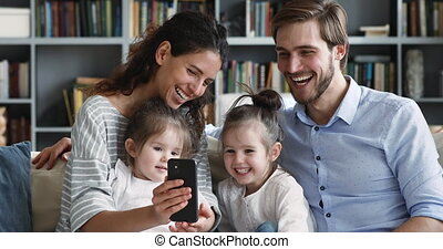 Happy parents showing funny app teaching kids using smart phone
