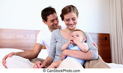 Happy parents sitting on bed with baby