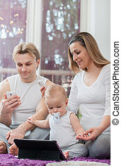 Happy parents sitting on the floor and playing with their baby boy. Computer era.