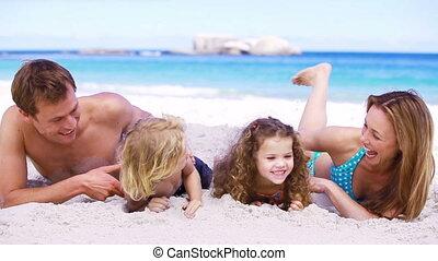 Happy parents tickling their children