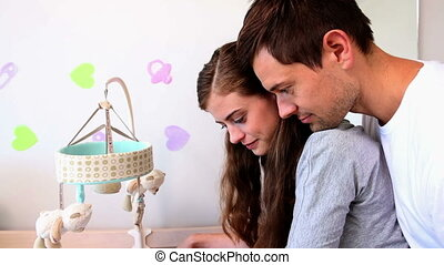 Happy parents watching over baby in crib