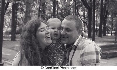 Happy parents with baby girl in a park