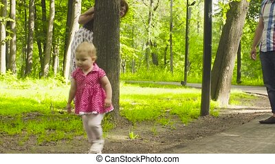 Happy parents with baby girl walking in a park