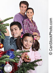 happy parents with children decorating Christmas tree