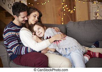 Happy parents with girl relaxing on the sofa