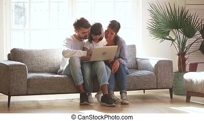 Happy parents with kid daughter using laptop in living room