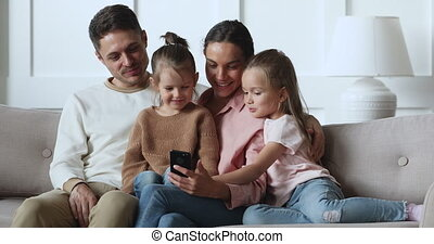 Happy parents with kids daughters relax on sofa using smartphone