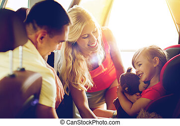 happy parents with little girl in baby car seat