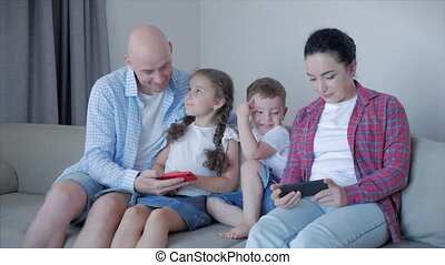 Happy parents with miles of small children play with at home,family embracing each other while sitting on a dwan at home having fun enjoying moments of joy using applications on their smartphone