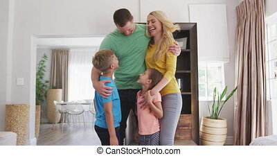 Happy parents with their children in a house