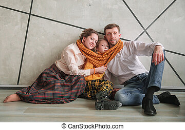 happy parents with their little daughter sitting on the floor in a new apartment.