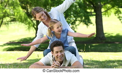 Happy parents with their little girl in the park on a sunny ...