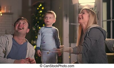 Happy parents with their son playing sitting on the bed in pajamas at Christmas A pillow fight at Christmas before the new year