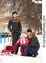 parents with toddler on sled in winter