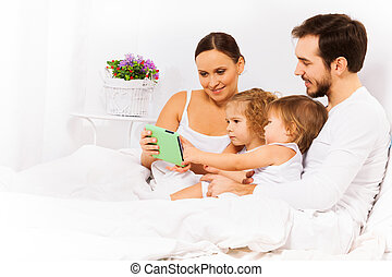 Happy parents with two kids look at tablet