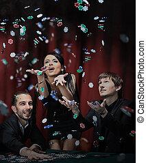 happy people celebrating winning in a casino