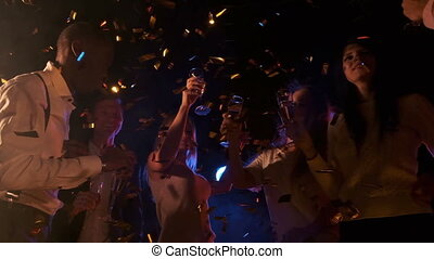 Having fun together. Group of beautiful young happy multi race people dance holding champagne in golden confetti and smiling nightlife new year celebration party