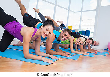 Happy people exercising on fitness mats at gym