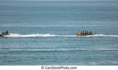 Happy people having fun on banana boat. Cool summer...
