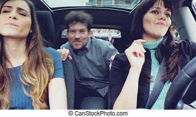 Happy people in car dancing