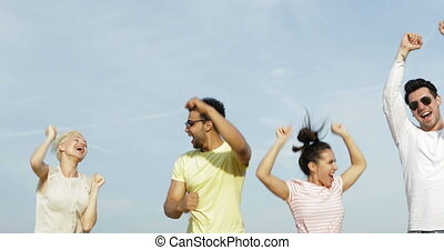 Happy People Jumping Over Blue Sky, Young Cheerful Friends...