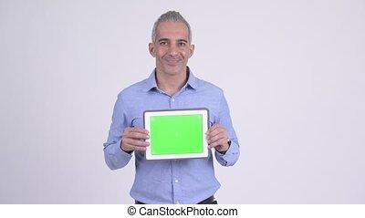 Happy Persian businessman showing digital tablet