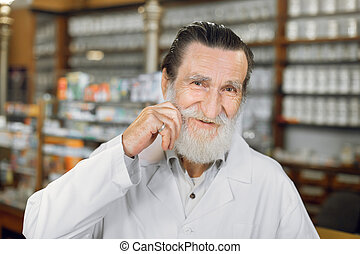 Happy pharmacist. Close up portrait of smiling handsome senior pharmacist touching his mustache, standing in ancient old pharmacy.