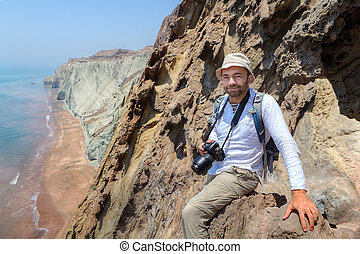 Happy photographer traveler sitting on the edge of a cliff.