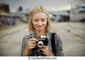young woman with small camera on the street
