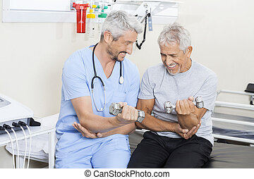 Happy Physiotherapist Assisting Senior Man In Lifting Dumbbells