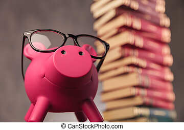 happy piggy bank wearing glasses looks up near books