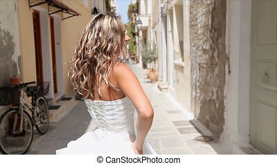 Happy playful bride against the background of narrow Greek streets. Newlyweds spend a honeymoon in Greece.