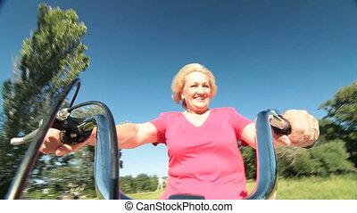 Happy playful senior woman having fun riding bicycle outdoors