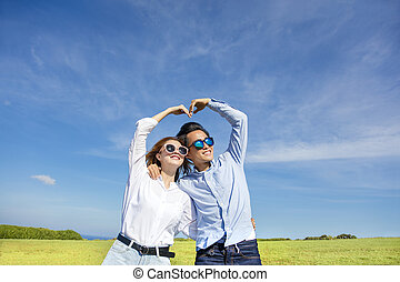 Happy playful young  couple forming love shape