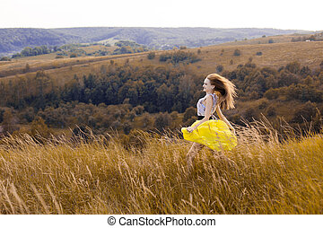 Happy playful young pretty girl running on the field with green, yellow wheat on the way to good life. Happy adventure in summer, summertime. Cheerful smiling girl in light yellow dress running on field