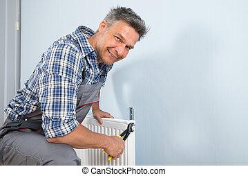 Happy Plumber Fixing Radiator