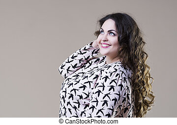 Happy plus size fashion model, fat woman on beige background